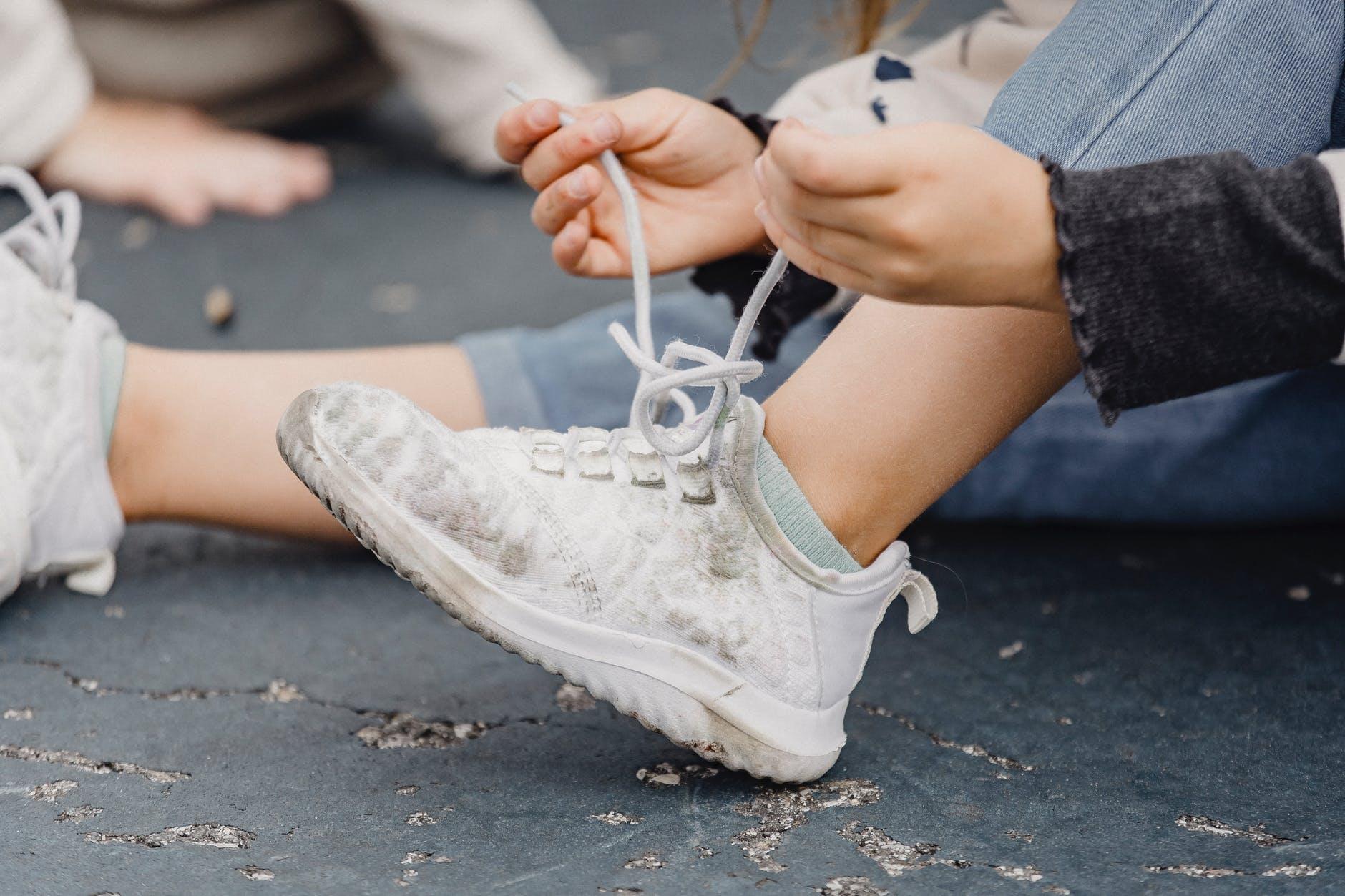 crop kid tying shoelaces on sneakers